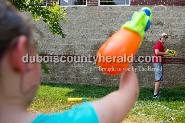 Sarah Ann Jump/The Herald Laurian Gayso of Ferdinand, 8, squirted Dubois County Bombers shortstop Ben Balgaard of Fenton, Mich. during Water Wars at the Ferdinand Public Library on Tuesday.