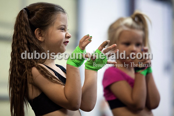 Alisha Jucevic/The Herald   Briley Moser of Bedford, 7, left, made a face at one of her teammates as her and Sterling Lyon of Jasper, 6, right, prepared for a stunt during the last day of stunt and pyramid camp on Monday morning at Full Out Tumble and Cheer in Jasper.