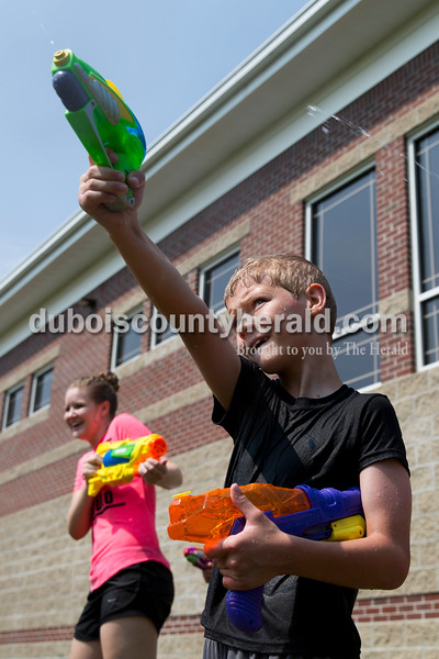 Sarah Ann Jump/The Herald Wyatt Crays of Ferdinand, 10, squirted his water gun and kept one for backup as Rockford Peach Natalie Altstadt of Huntingburg aimed at him, during Water Wars at the Ferdinand Public Library on Tuesday.