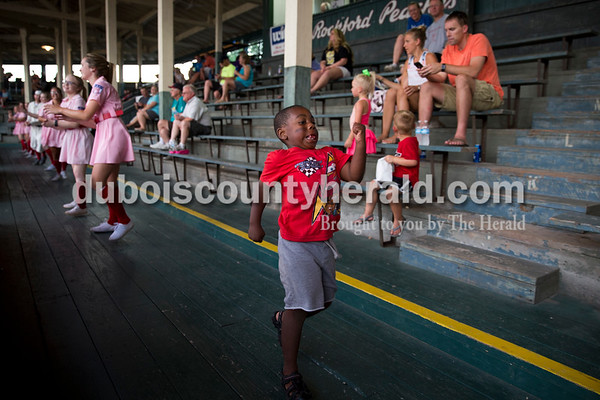 """Martin Cook of Santa Claus, 3, danced as the Rockford Peaches performed a line dance to """"Cotton Eye Joe"""" during Thursday evening's game against the Owensboro Oilers at League Stadium in Huntingburg. The Bombers lost 12-3. Sarah Ann Jump/The Herald"""