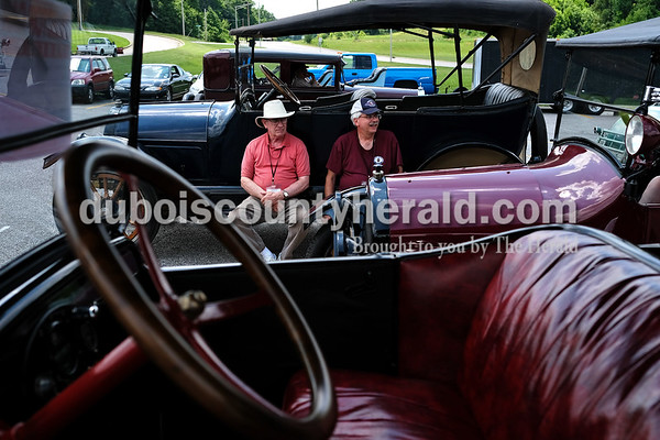 Dave Weatherwax/The Herald Steve Kemper of Alexandria, Ky., left, and David Allen of Edgewood, Ky.,  sat on the running boards of a 1917 Overland automobile Monday afternoon as they waited to go on an outing with the Willys-Overland-Knight Registry.