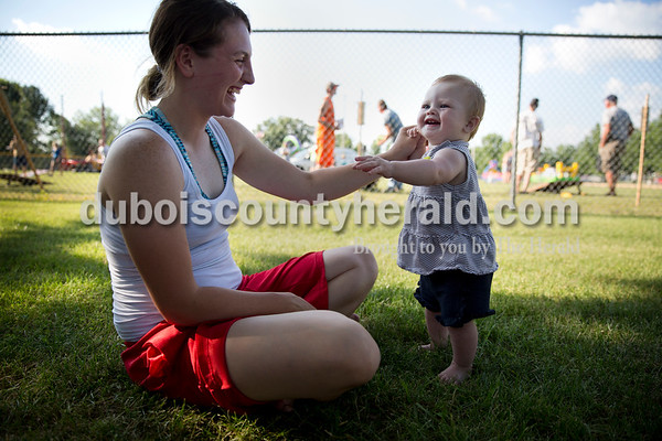Autumn Bye of Odon helped her daughter Addison, 9 months, dance  as they at in the shade to watch Addison's father, TJ Miller, compete in the corn hole tournament during Ferdinand Heimatfest at 18th Street Park on Friday. Sarah Ann Jump/The Herald