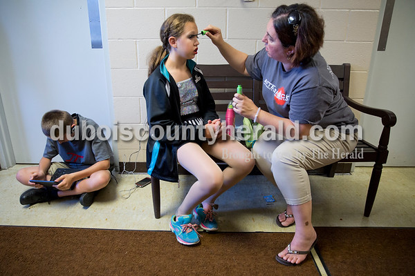 """Sarah Ann Jump/The Herald Kara Greenwood of Santa Claus applied mascara to her daughter Sophia, 12, as Logan Hostetter of Jasper, 12, watched a movie before Sunday's Dance Central Academy of Performing Arts """"Got 2 Dance"""" recital at Jasper Arts Center."""