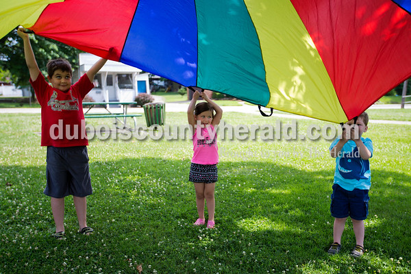 Alisha Jucevic/The Herald   Children gathered on the Jasper Public Library front lawn for an outdoor fun day on Monday, the official first day of summer. Reznor Blair, 8, Brynlee Rollins, 3, and Dustin Bleemel, 3, all of Jasper,  worked together to lift a colorful parachute during the outdoor event. The children also participated in a bean bag toss, hula hoop games, a water balloon toss and colored popsicles.