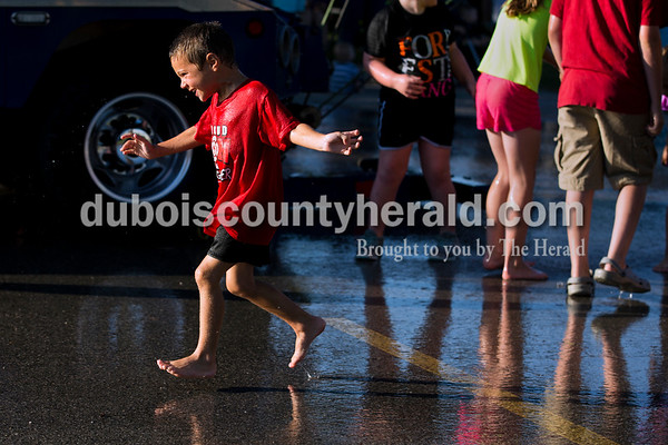 Carson Kippenbrock of Ferdinand, 4, ran in the water spray during the firefighters' waterball competition at Ferdinand Heimatfest at Ferdinand Community Center on Friday. Sarah Ann Jump/The Herald