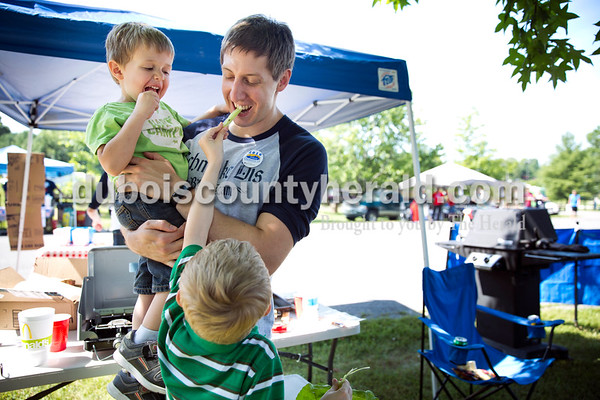 """Ben Potter of Jasper held his son Jack, 3, as his son Alex, 6, fed him a Swiss chard stalk at their family's """"Schmoke Dis"""" barbecue team tent during the Backyard BBQ competition at Ferdinand Heimatfest at 18th Street Park in Ferdinand on Saturday. """"I call it celery because it tastes exactly the same,"""" said Alex about the Swiss chard. Ben participated in the barbecue competition with his brother, sister, brother-in-law and father. Alex said he is a future barbecuer. Sarah Ann Jump/The Herald"""