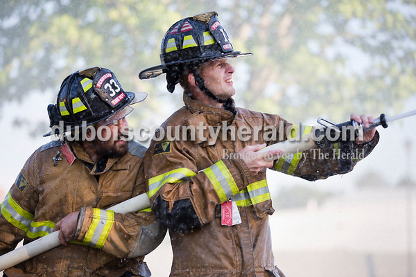 Chris Schipp, right, aimed the hose as Doug Lindauer, both of Ferdinand, helped hold it during the firefighters' waterball competition at Ferdinand Heimatfest at Ferdinand Community Center on Friday. Sarah Ann Jump/The Herald