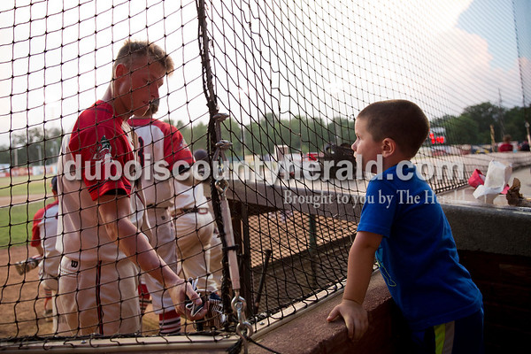 Holden Lingenfelter of Loogootee, 4, watched the players through the net in hopes that they would give him a ball during Thursday evening's game against the Owensboro Oilers at League Stadium in Huntingburg. The Bombers lost 12-3. Sarah Ann Jump/The Herald