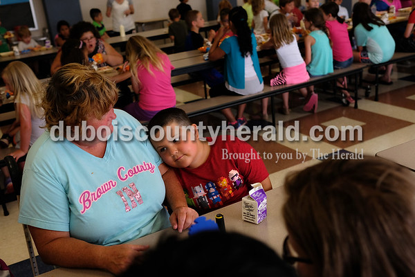 Dave Weatherwax/The Herald Joshua Lawrence of Huntingburg, 5, cuddled up against his mother, Rita, after he finished eating his lunch Tuesday at Huntingburg Elementary School. Rita brings her son on during the summer to the school for the free lunches offered two days a week to school-aged children and special-needs adults.