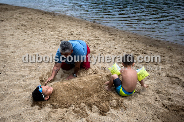 """Alisha Jucevic/The Herald   Gloria Villarreal of Ferdinand and her grandson Armando Luna of San Antonia, Texas, 5, covered Luna's cousin, Ya'hirr Fierro, 6, of Ferdinand in the sand as they waited for more family to arrive on Wednesday afternoon at the Ferdinand State Forest Lake. Villarreal said it was too hot inside so the family decided to get outside for a swim and cookout. """"I like it here because it's quiet,"""" she said. """"It's good for the children to get out of the house."""""""