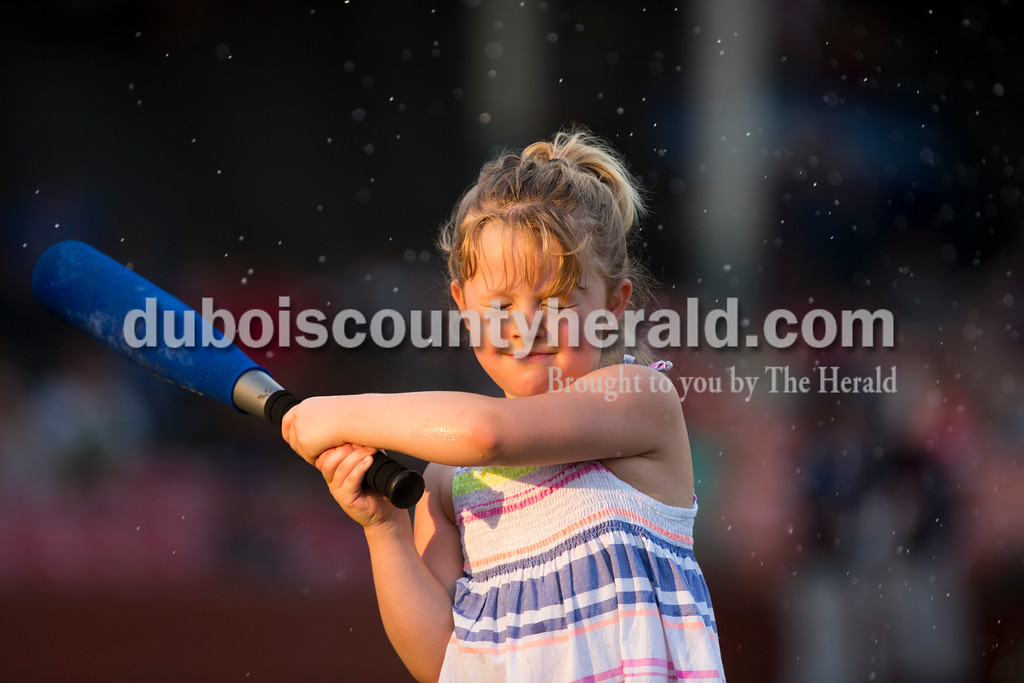 Gwen Stinson of Velpen, 5, hit water balloons with a bat between innings during Thursday evening's game against the Owensboro Oilers at League Stadium in Huntingburg. The Bombers lost 12-3. Sarah Ann Jump/The Herald