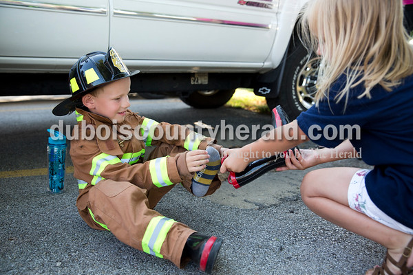 Gavin Schipp, 5, put on his boots with the help of Adrian Reckelhoff, 4, both of Ferdinand, before the firefighters' waterball competition during Ferdinand Heimatfest at Ferdinand Community Center on Friday. Gavin's mother Jenny Schipp said she purchased the fireman's uniform, which says Schipp on the back, just for occasion. Gavin practices waterball at home with a garden hose and ball, so that he can be like his father Chris Schipp, a Ferdinand firefighter participating in the competition. Sarah Ann Jump/The Herald