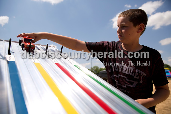 Camren Giesler of Ferdinand, 12, placed his car on the track during the Pinewood Derby at Ferdinand Heimatfest at 18th Street Park on Saturday. Sarah Ann Jump/The Herald