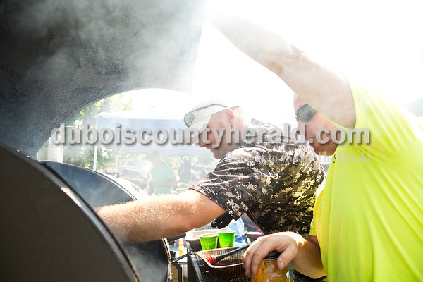 Brian Partenheimer of Ferdinand, center, checked on the meat as Jason Mattingly of Mariah Hill, right, held up the cover of the smoker as they competed in the Backyard BBQ competition with the High Life Hunt Club team at Ferdinand Heimatfest at 18th Street Park on Saturday. Sarah Ann Jump/The Herald