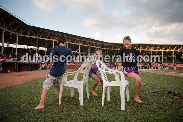 Evan Breitwieser of Jasper, 9, left, Maya Anderson of Huntingburg, 8, and Bella Beckman of Dubois, 9, played musical chairs in between innings during Thursday evening's game against the Owensboro Oilers at League Stadium in Huntingburg. The Bombers lost 12-3. Sarah Ann Jump/The Herald