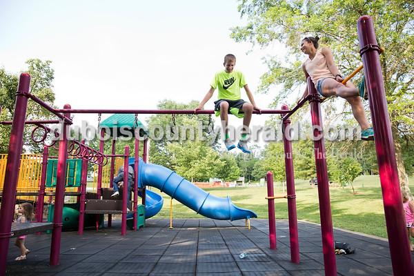 Garrett Betz of Schnellville, 15, left, Claire Mehling of Ferdinand, 15, climbed on the playground during Ferdinand Heimatfest at 18th Street Park on Saturday. Sarah Ann Jump/The Herald