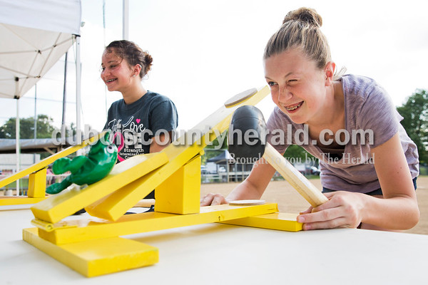 """Abby Eckert of Schnellville, 14, right, lined up her catapult as she played the """"Launch the Frog"""" game with Rachel Thomas of St. Anthony, 14, left, during Ferdinand Heimatfest at 18th Street Park on Friday. Sarah Ann Jump/The Herald"""