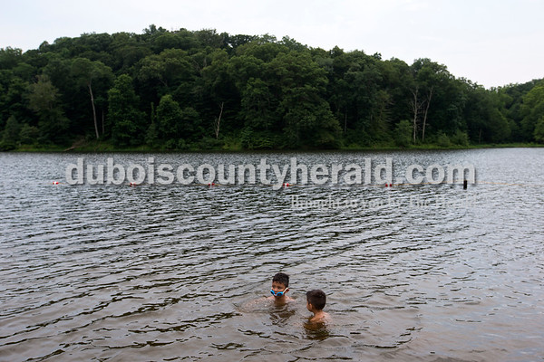 """Alisha Jucevic/The Herald   Cousins Ya'hirr Fierro, 6, of Ferdinand, left, and Armando Luna of San Antonia, Texas, played in the water together on Wednesday afternoon at the Ferdinand State Forest Lake. Their grandmother, Gloria Villarreal of Ferdinand said it was too hot inside so they decided to get outside for swimming and a cookout. """"I like it here because it's quiet,"""" she said. """"It's good for the children to get out of the house."""""""
