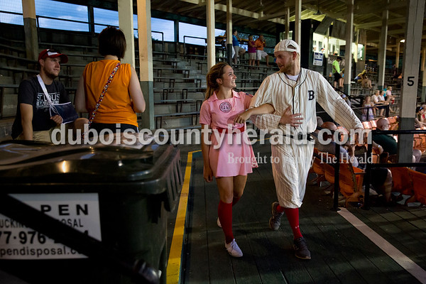Rockford Peach Shania Mundy of Lincoln City and Corey Oser of Holland, dressed as the Bombers' mascot Casey, walked arm-in-arm around the stadium during Thursday evening's game against the Owensboro Oilers at League Stadium in Huntingburg. The Bombers lost 12-3. Sarah Ann Jump/The Herald