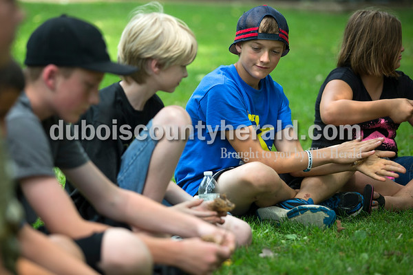 Alisha Jucevic/The Herald   Will Weinzapfel, 13, left, Cameron Crawford,10, Blake Danzer, 13, and Kylene Danzer, 10, all of Jasper, broke apart tree bark to create a natural fire tinder during a wilderness survival skills class taught by Clint Jivoin of Moores Hill and hosted by the Jasper Public Library at the Dave Buehler Plaza on Thursday afternoon in Jasper. Jivoin shared techniques and materials used for four important elements of wilderness survival: shelter, water, fire and food.