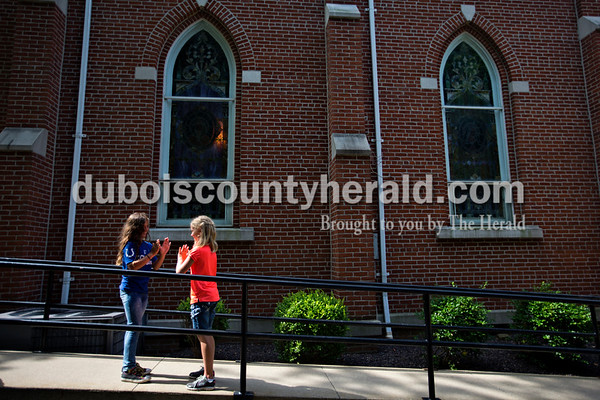 Alisha Jucevic/The Herald   Makenzie Buchta, 9, and Isabella Harmon, 9, both of Jasper, made up a handshake together outside Saint Mary's Parish in Ireland on Tuesday morning during the second day of vacation bible school.