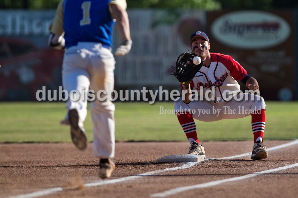 Alisha Jucevic/The Herald <br /> <br /> Bombers' Zach Gray caught the ball as Muhlenberg County's JD Roberts ran late to first during Tuesday night's game at League Stadium in Huntingburg. The Bombers won 10-2.