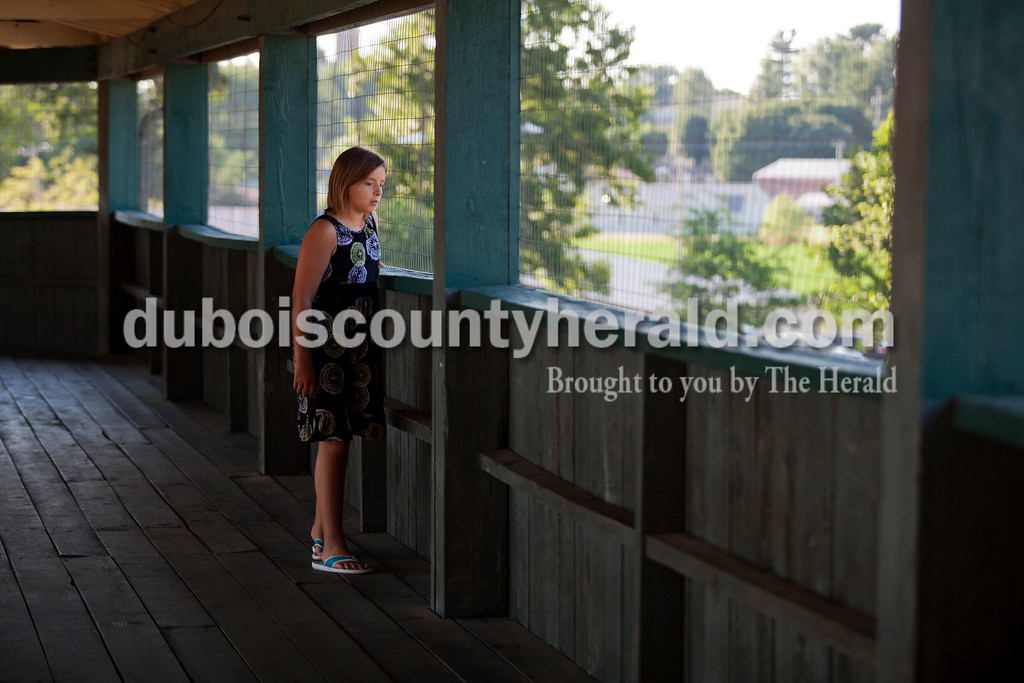 Alisha Jucevic/The Herald <br /> <br /> Cadi Herzog of Jasper, 10, watched passersby from the balcony at League Stadium during Tuesday night's Bombers game against the Muhlenberg County Stallions in Huntingburg.