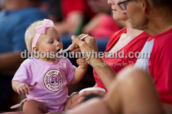 Sarah Ann Jump/The Herald Kate Nichols of Evansville, 9 months, was fed ice cream by her grandfather Paul Tempel of Dale as she sat on the lap of her mother Alicia Nichols during Wednesday evening's Dubois County Bombers game against the Muhlenberg County Stallions at League Stadium in Huntingburg. Tempel hosts a Bombers player and Wednesday as Host Appreciation Night.