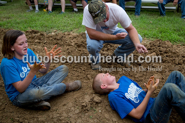 Sarah Shaw/The Herald  John Seger of St. Henry gave advice on how to hold the rope while Kayli Hoffman of Jasper, 12, and Carter Giesler of Ferdinand, 10, clapped their hands together to rub in a sticky residue that helps with gripping the rope before the tug-of-war competition at the Dubois County 4-H Fairgrounds in Bretzville on Thursday evening.