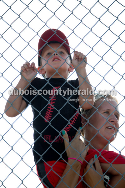 Sarah Shaw/The Herald  Caleb Mehringer of Jasper, 4, rested on his mom Alicia's shoulder to watch his siblings compete in the swim portion of the Dubois County Youth Triathlon and Duathlon on Saturday at Huntingburg City Park.