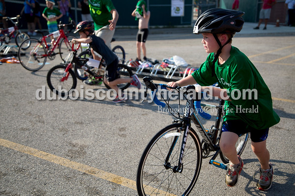 Sarah Shaw/The Herald  Ridley Cecil of Owensboro, Ky., 7, pushed his bike from the transition area during the Dubois County Youth Triathlon and Duathlon on Saturday at Huntingburg City Park.