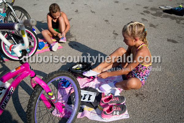 Sarah Shaw/The Herald  Nora Breitwieser of Jasper, 7, and Adilynn Mehringer of Jasper, 8, quickly put their shoes on before beginning the bike portion of the Dubois County Youth Triathlon and Duathlon on Saturday at Huntingburg City Park.