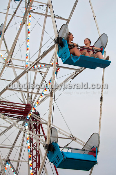 Bailee Fisher, 16, left and Jenna Broeker, 17, both of Huntingburg, chatted as they circled around the in Ferris wheel Wednesday evening at the Dubois County 4-H Fair in Bretzville.  Alisha Jucevic/The Herald