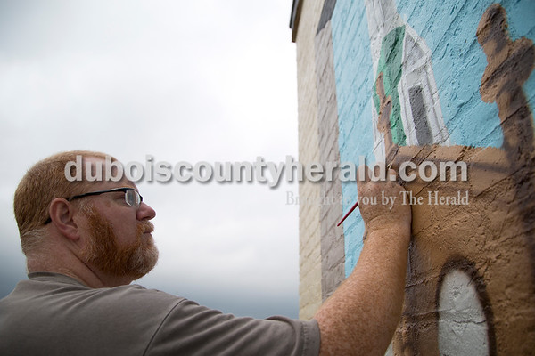 Sarah Shaw/The Herald  Michael Smith of Chandler painted details on the Saint Joseph Catholic Church tower depicted in the new mural commissioned by the Jasper German Club on the corner of 6th and Newton streets on Wednesday. Weather and equipment malfunctions have delayed Smith, who hopes to have the mural completed within the next two weeks.