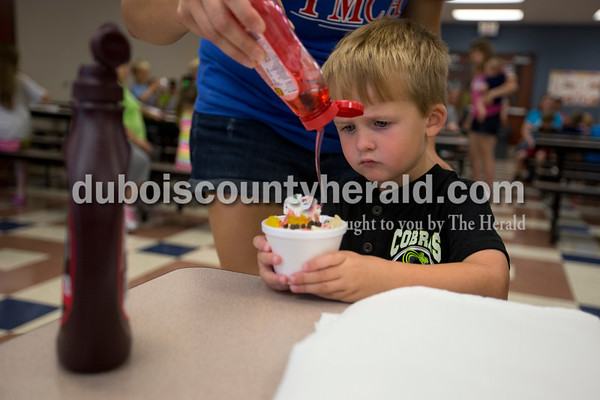 Jennifer Schaeffer of Huntingburg squeezed a spiral of fruit syrup for her son Korbin, 3, at the Huntingburg Public Library ice cream bash on Thursday at Holland Elementary.   Alisha Jucevic/The Herald