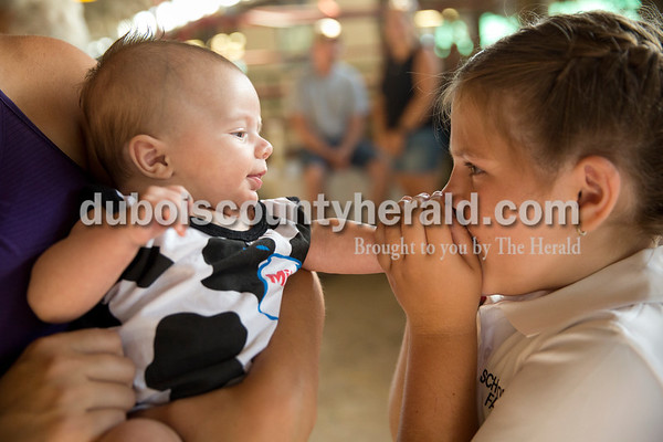 Sarah Ann Jump/The Herald Lyndsey Taylor of St. Henry, 9, right, played with her 3-month-old brother Jaxson Schwoeppe, held by their mother Stefanie Kunkler, before the dairy show at the Dubois County 4-H Fairgrounds on Tuesday morning.