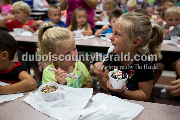 Raylee Forler of Santa Claus, 3, and Layla Greurich of Holland, 5, enjoyed ice cream sundaes at the Huntingburg Public Library ice cream bash on Thursday at Holland Elementary.   Alisha Jucevic/The Herald