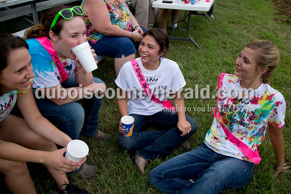 Sarah Shaw/The Herald  4-H Fair Queen and Teen Miss contestants Jennifer Merkley of St. Anthony, 18, Brianna Lammers of Huntingburg, 19, Katelyn Tretter of Ferdinand, 16, and Melanie Roberts of Hillham, 17, joked around before the start of the tug-of-war competition at the Dubois County 4-H Fairgrounds in Bretzville on Thursday evening.