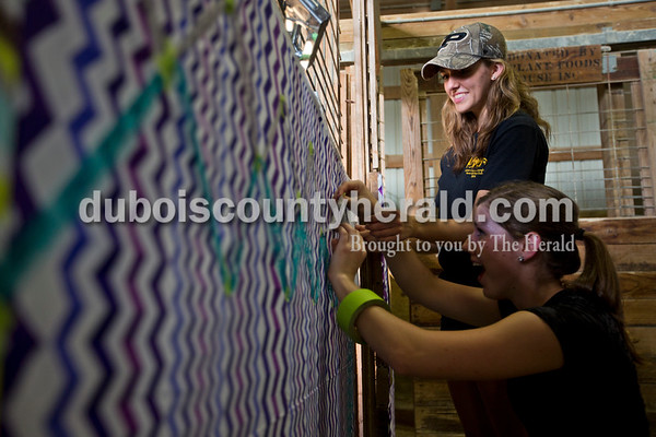 Kelcie Hassfurther of Schnellville helped her friend Clarissa Weyer of Ferdinand, 16, decorate Weyer's stable Monday evening during animal check in at the Dubois County 4-H  Fairgrounds in Bretzville. Hassfurther graduated last year and is now a first year leader. To ease her sadness of growing out of the program, Weyer said she jumped at the opportunity to help decorate Weyer's stable.   Alisha Jucevic/The Herald