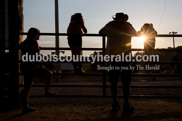 Rita Wagner and her husband Bernie of Bretzville leaned against a fence to watch the horse performance show with their granddaughters, Mollie Combs, 7, left, and Maci, 3, both of Birdseye in the horse barn Wednesday evening at the Dubois County 4-H Fair in Bretzville.  Alisha Jucevic/The Herald