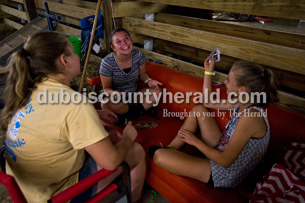 Ella Goeppner of Jasper, 13, left, April Decesaro of Bethany, Ill., center, and Katie Stenftenagel of Jasper, 13, played cards Wednesday night at the Dubois County 4-H Fair in Bretzville. Stenftenagel said she usually stays at the fairgrounds until about midnight before heading home, and to pass the time she often plays cards with friends.  Alisha Jucevic/The Herald