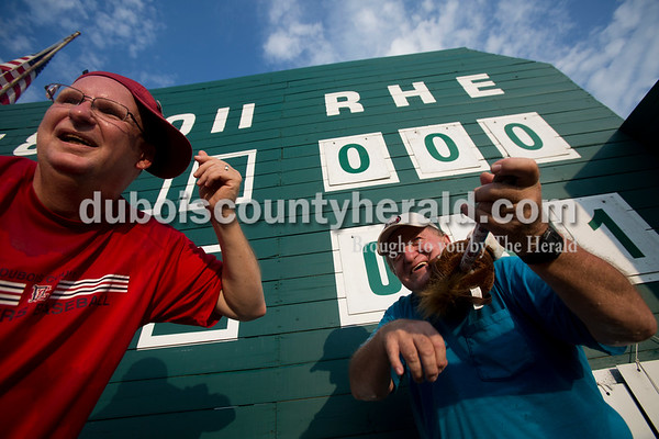 """Sarah Ann Jump/The Herald Darren Howard of Jasper, left, known as """"Curly"""", and Steve Blessinger of Huntingburg, known as """"Mo"""", pretended to play music from the manual scoreboard platform as Casey, the Bombers' mascot, ran around the field between innings during Wednesday evening's Dubois County Bombers game against the Muhlenberg County Stallions at League Stadium in Huntingburg. The Bombers won 5-1. Blessinger first earned the nickname Mo in high school, and Howard became Curly when he started helping Blessinger with the manual scoreboard two years ago. As a kid, Howard used to run the manual scoreboard while his father coached the Jasper High School baseball team."""