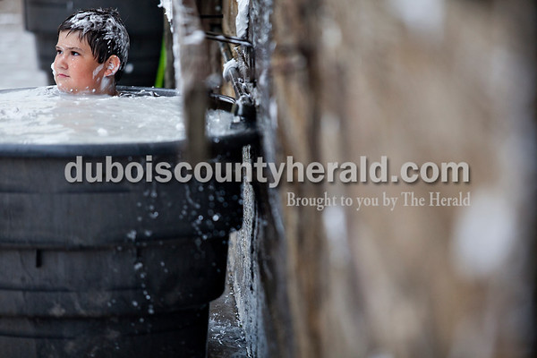 Will Werner of Ferdinand, 11, washed the shaving cream off his clothes in a trough during the annual shaving cream fight on Thursday morning at the Dubois County 4-H Fairgrounds in Bretzville.   Alisha Jucevic/The Herald