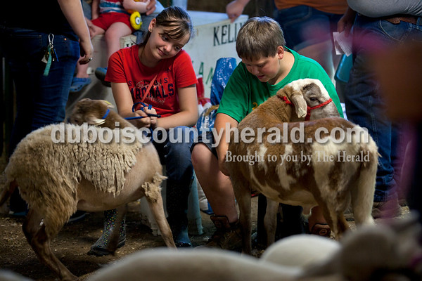 Riley Beckman of Jasper, 12, and Kasey Verkamp of Dubois, 12, waited in line together during animal check in Monday evening at the Dubois County 4-H Fairgrounds in Bretzville.    Alisha Jucevic/The Herald