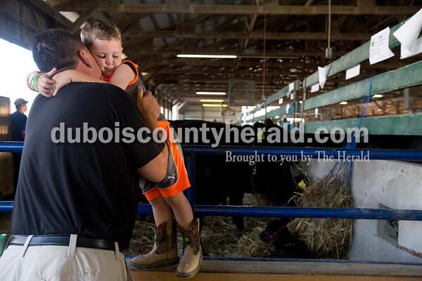 Sarah Ann Jump/The Herald Quinten Schue of Jasper, 4, hugged his uncle Scott Fischer at the Dubois County 4-H Fairgrounds in Bretzville on Thursday.