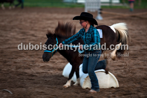 Mary Seybold of Cuzco, 10, led Thunder over jumps during the miniature horse jumping class Wednesday evening at the Dubois County 4-H Fair in Bretzville.  Alisha Jucevic/The Herald