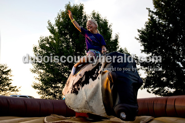 Aurora Jacob of Ferdinand, 7, took a turn on the mechanical bull Wednesday evening at the Dubois County 4-H Fair in Bretzville.  Alisha Jucevic/The Herald