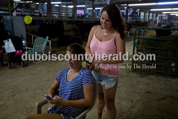 Claudia Schuetter, 18, braided Michelle Helming's hair, 20, both of Ferdinand, as they chatted in the dairy barn Wednesday night at the Dubois County 4-H Fair in Bretzville.  Alisha Jucevic/The Herald