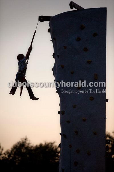 Izak Meyer of St. Anthony, 7, pushed out from the climbing wall to slide back down to the ground Wednesday evening at the Dubois County 4-H Fair in Bretzville.  Alisha Jucevic/The Herald
