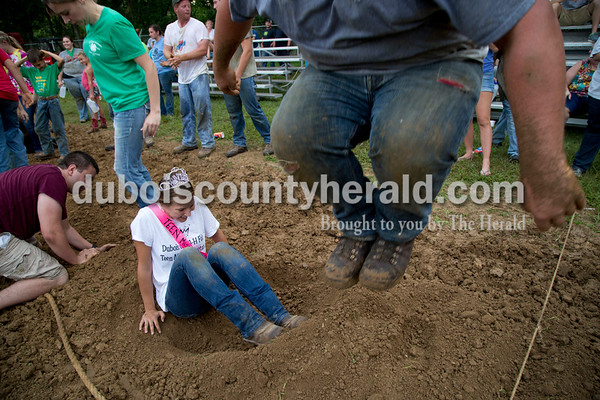 Sarah Shaw/The Herald  Ethan Schwoeppe of Huntingburg jumped to pack down the dirt while helping Teen Miss Jaylyn Giesler of Huntingburg, 15, dig her hole during the tug-of-war competition at the Dubois County 4-H Fairgrounds in Bretzville on Thursday evening.